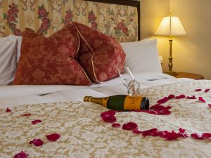 An image of a bed at the Coul House Hotel with a champagne bottle and rose petals scattered in the shape of a love heart.