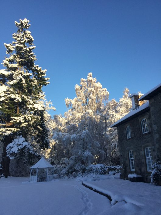 An image of the Coul House Hotel and gardens with blue sky and snow.