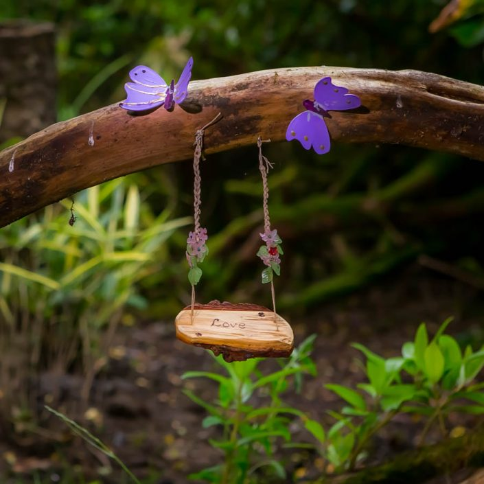 An image of a miniature swing with a carving of 'Love' from the Coul House Hotel Fairy Garden